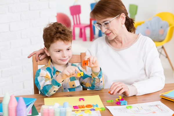 Older woman helping autistic child wth play letters at a desk.