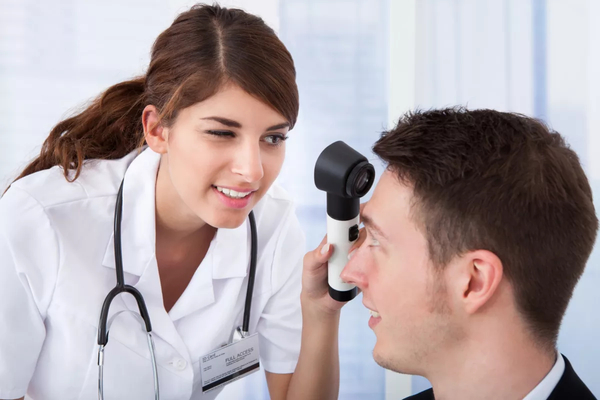 Woman dermatologist examining the skin on a man's forehead.