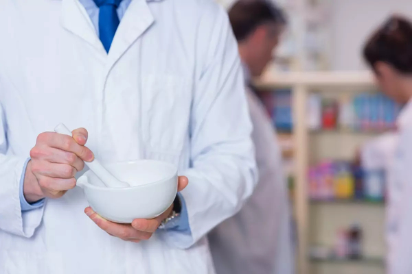 Pharmacist at Health First! Integrative Medicine Pharmacy holding a mortar and pestle.
