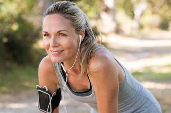 Woman wearing ear phones taking a break from jogging.