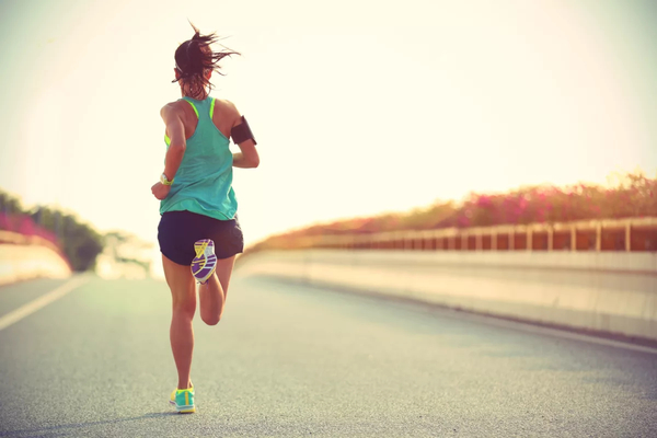 Woman running on a road after recovering from a sports related injury with the help of personalized medicine from Health First Integrative Medicine Compounding Pharmacy in Windsor, CA.