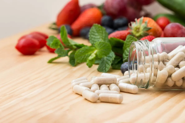 Vitamin capsules on a wooden table with a variety of fresh fruit.