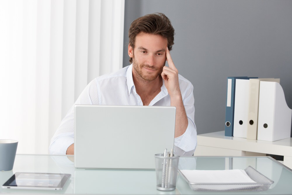 Man at a desk thinking about how testosterone supplementation may benefit him.