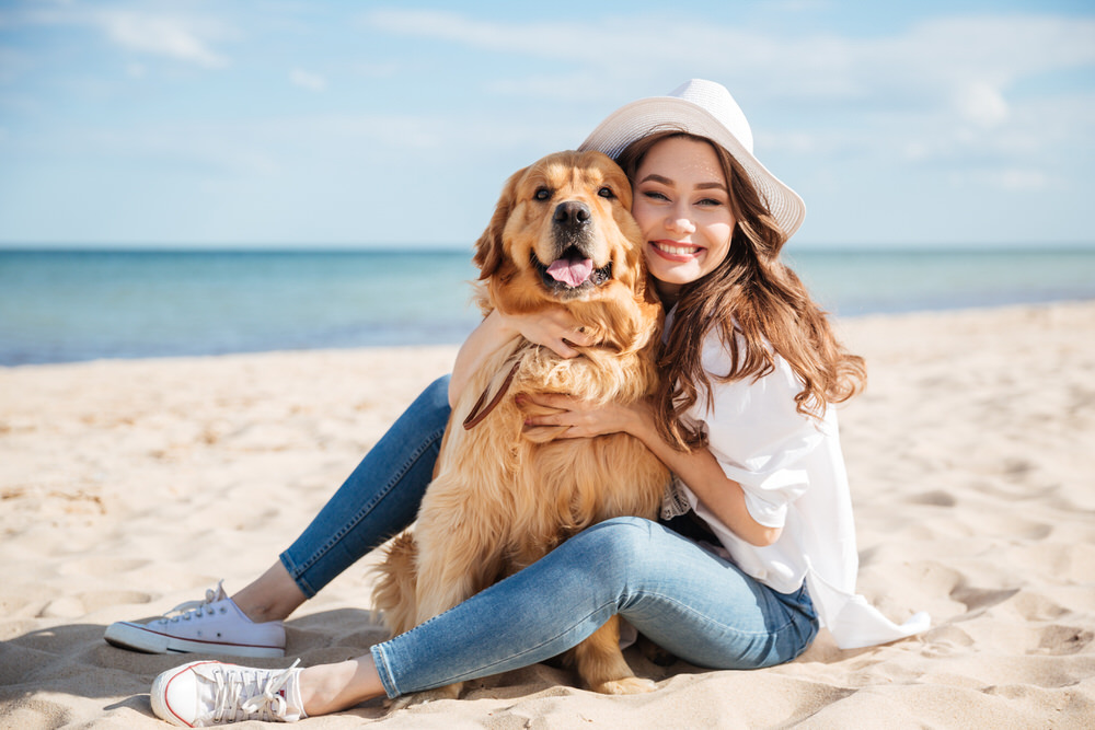 Woman sitting down, holding her dog at the beach, after receiving custom pet medications from Health First Pharmacy in Windsor, CA.