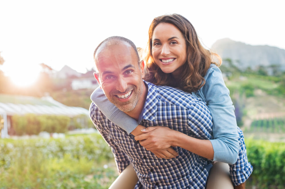 Middle aged man carrying his wife on his back after receiving testosterone replacement from Health First! Pharmacy.
