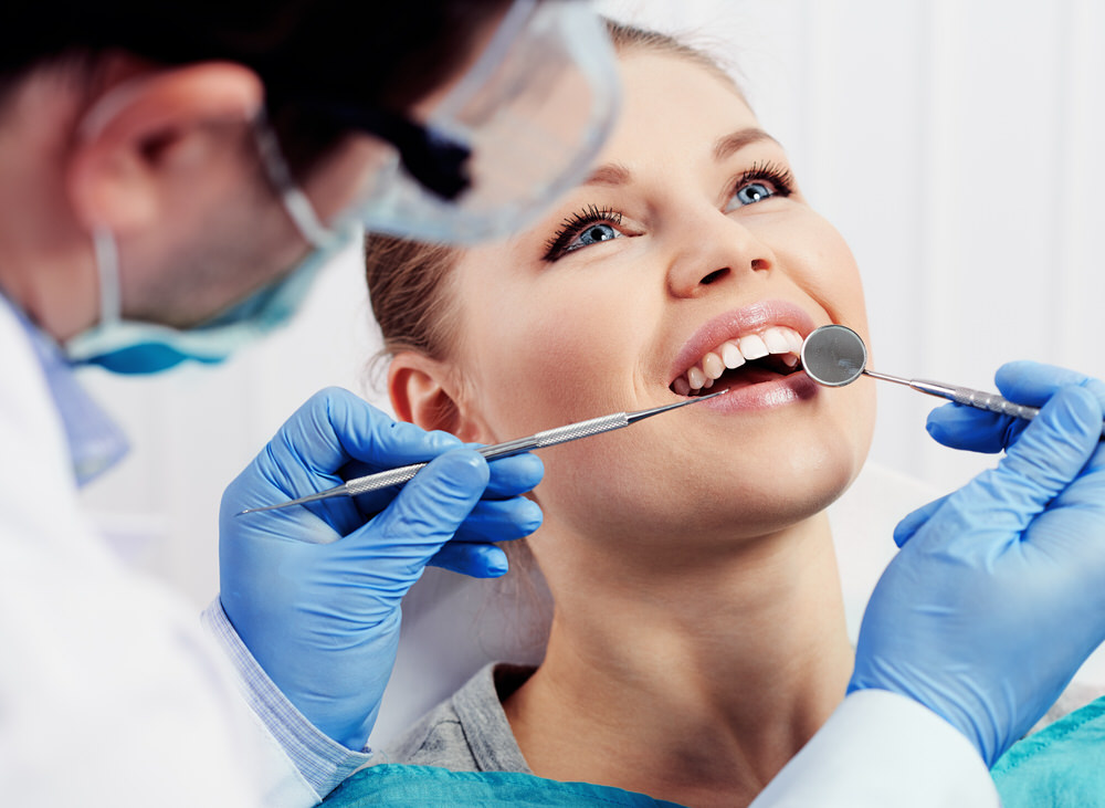 Smiling woman at being examined by dentist
