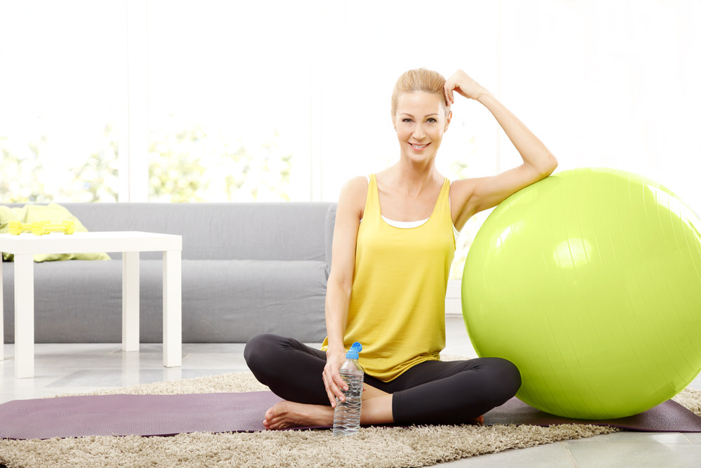 Women smiling leaning against exercise ball.